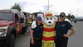 Photo of Firefighter Tiffany Hamdan, a person wearing a Sparky the dog mascot costume, and Firefighter Jessica Barrett