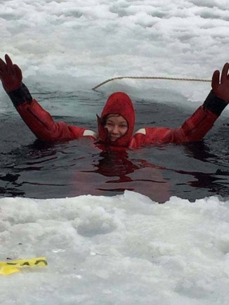 Photo of Firefighter Tiffany Hamdan in a dry suit during ice rescue training in a hole cut in a frozen lake