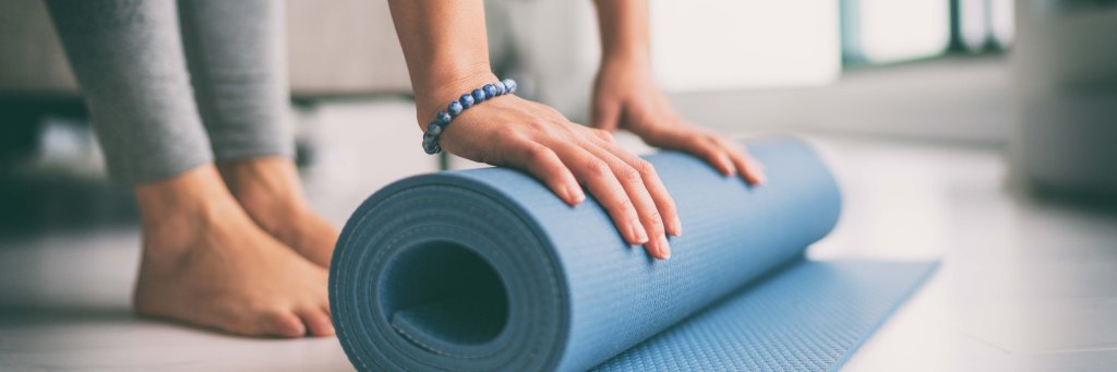 Yoga at home active lifestyle woman rolling exercise mat in living room for morning meditation yoga
